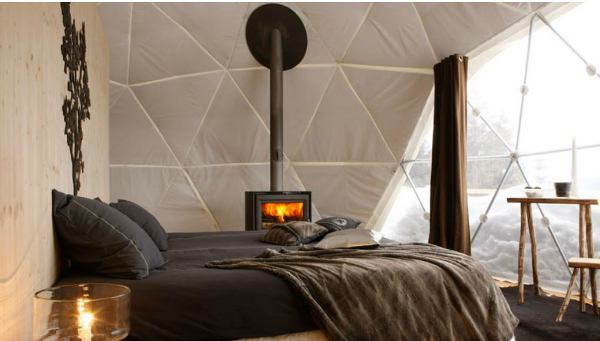 Whitepod features 40 pod-like tents equipped with a wood stove, comfortable bed and full bathroom.